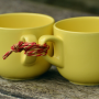 two yello coffee cups tied together with red string